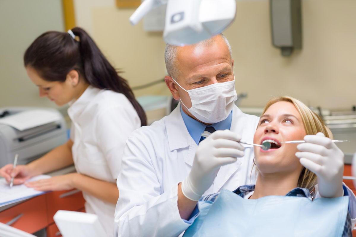 стоматолог осматривает пациента